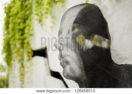 MOSCOW, RUSSIA - JUN 26, 2015: Sculpture in Sokolniki park. Human face made of metal mesh mounted into the concrete block.