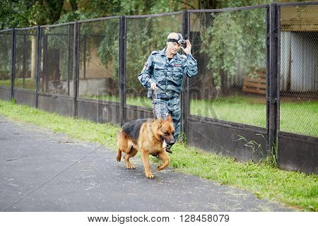 MOSCOW, RUSSIA - JUN 26, 2015: Policeman in camouflage with head camera runs with dog along fence during training.