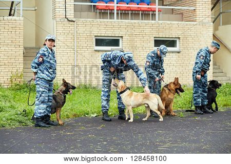 MOSCOW, RUSSIA - JUN 26, 2015: Policemen with dogs at courtyard of police department.