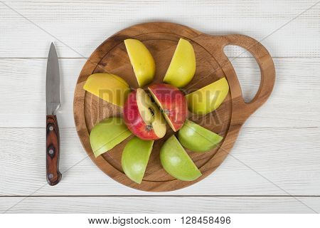 Composition of apple pieces on wooden cutting board and a knife next to it in top view. Healthy food. Boosting immune system. Table setting. Improving health. Food decoration. Natural source of iron for anemia.