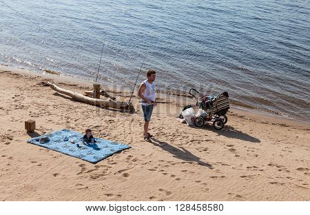 SAMARA RUSSIA - MAY 15 2015: Man with the child fishing on the fishing rod on the bank of the Volga River in Samara