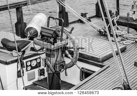 Steering wheel and deck of the old boat, close-up