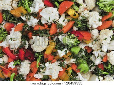 Fresh vegetable salad with cauliflower, broccoli, carrots and peppers, overhead view closeup