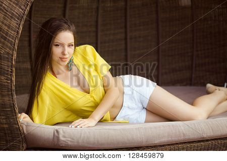 Beautiful young woman in yellow t-shirt and white shorts relaxing on chaise lounge near swimming pool