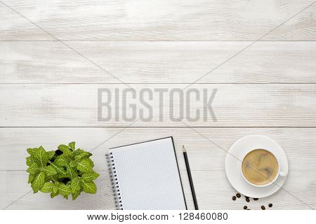 Workplace with cup of coffee, indoor plant, empty notebook and pencil on wooden surface in top view. Office workplace. Vivacity in the mornings. Keeping healthy. Coffee breakfast. Increase working efficiency. Improving mood and productivity. Reducing stre