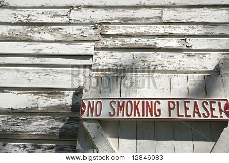 "Sign on old white peeling building reading ""No smoking please!""."