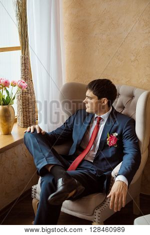 Gorgeous serious groom. Handsome man in a suite with a buttonhole sitting on chair and looking in window indoors