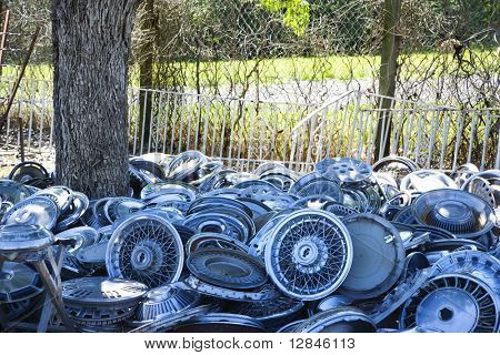 Stacks of old hubcaps on the ground next to tree.