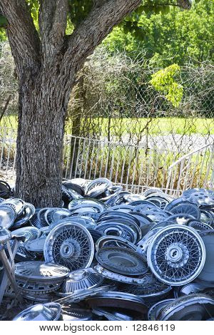 Pile of old hubcaps on the ground next to tree.