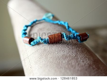 A handmade bracelet made of blue hemp cord with wooden beads.