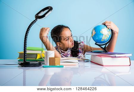 indian girl student looking at educational globe and sitting at table with books, table lamp and milk mug, asian girl child studying geography, curious asian girl studying geography with globe