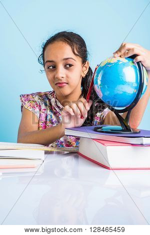 indian girl student studying, looking at educational globe and sitting at table with books, table lamp and milk mug, asian girl child studying geography, curious asian girl studying geography with globe