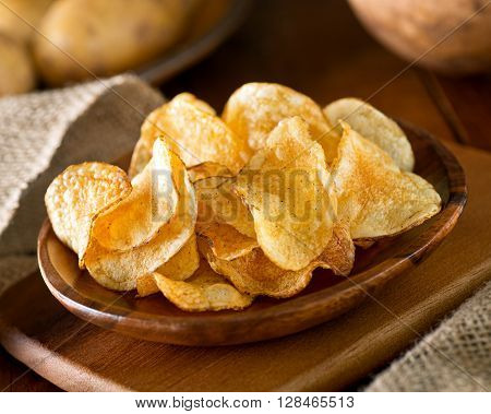 Delicious home made potato chips with sea salt and black pepper against a rustic background.