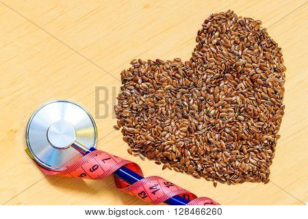 Diet healthcare weight reduction concept. Flax seeds linseed heart shaped stethoscope and measuring tape. Healthy food for preventing heart diseases overweight.
