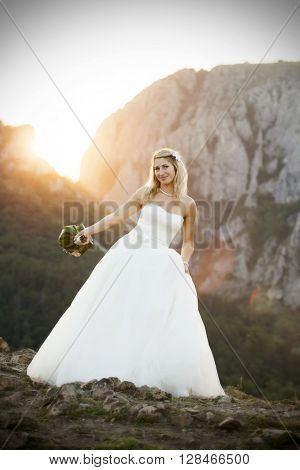 Smiling bride holding big wedding bouquet n the sunset