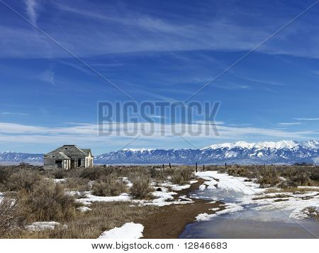 Scenic landscape in rural snowy Colorado of abandoned house.