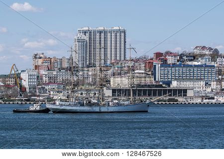 sailboat moored by a tugboat in the port of Vladivostok