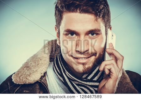 Portrait of young man with half shaved face beard hair talking on mobile phone. Handsome guy on blue. Communication technology. Instagram filter.