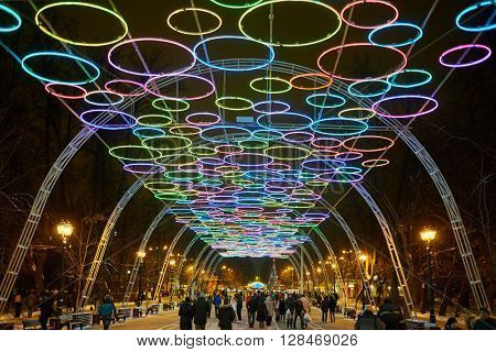 RUSSIA, MOSCOW - DEC 28, 2014: People walk on illuminated alley in Sokolniki park in the evening on the eve of New Year.