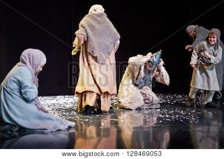 MOSCOW, RUSSIA - JAN 15, 2015: Praying women and beggars on square in front od Cathedral on stage of Moscow theatre Et Cetera in play Boris Godunov directed by Peter Stein.