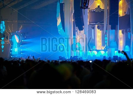 RUSSIA, MOSCOW - JUN 12, 2015: DJ on central stage and dancing people on dance floor around and at grandstands during Sensation Wicked Wonderland show at Olympiysky sports complex.