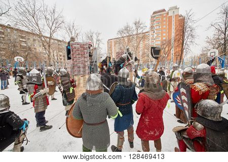RUSSIA, MOSCOW - DEC 28, 2014: Warriors dressed in defensive equipment attack castle during historic reenactment battle on Military History maneuvers on Taganka.