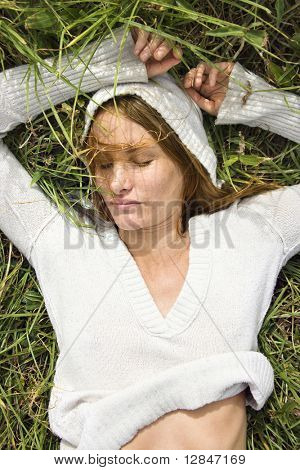 Portrait of attractive young redheaded woman lying in grass resting.