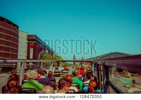 HAMBURG, GERMANY - JUNE 08, 2015: Sightseeing bus visiting all the turistics places in Hamburg, historic buildings on the sides on a sunny day