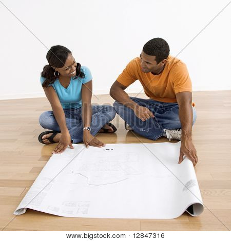 African American male and female couple sitting on floor looking at architectural  blueprints.