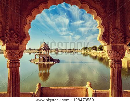 Vintage retro effect filtered hipster style image of Indian landmark Gadi Sagar - artificial lake view through arch. Jaisalmer, Rajasthan, India