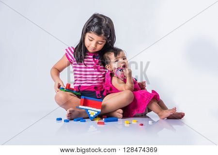 indian small girls or asian small siblings playing with colourful blocks over white background, cute little indian girl baby sitting or taking care of younger sister, two small indian sisters playing