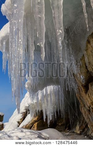 Huge icicles on a cliff. Beautiful winter landscape in the Lake Baikal.