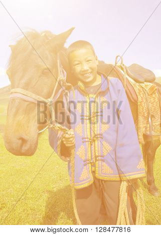 Little boy tilting his head to his horse and smiling at outdoors.
