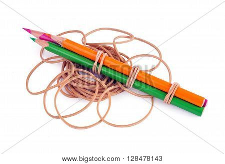 Pink orange and green colour pencils are tied with rubber bands