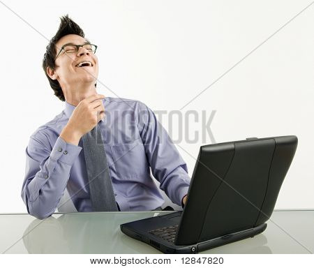 Asian businessman sitting at desk working on laptop computer laughing.