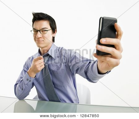 Businessman taking photograph of himself using pda or smart phone device.