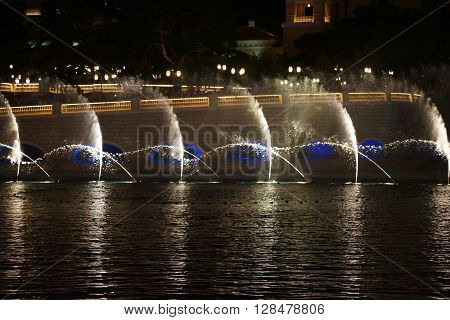 LAS VEGAS, USA - DECEMBER 23, 2015: The famous fountain show in front of the Bellagio luxury hotel with water fountains and colorful lighting on Las Vegas Boulevard on the night of December 23, 2015 in Las Vegas.