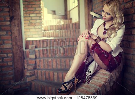 The blond sexy girl dressed in elegant clothes in the style of ethnic on a background of old brick walls
