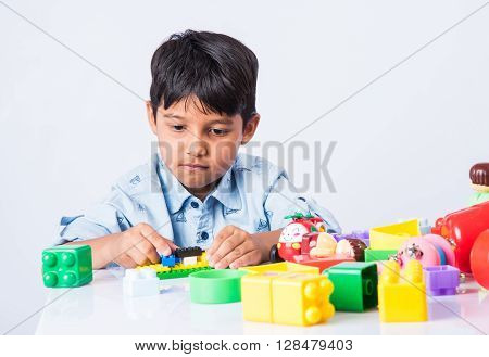 indian kid playing with block toys, asian small boy playing indoor games, colorful plastic block toys, making toy house, over white background, indian small boy playing blocks