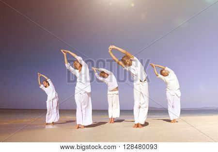 People performing yoga on the beach.