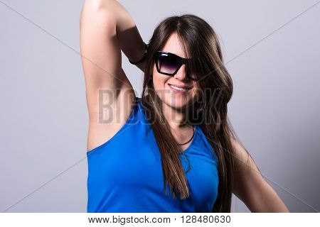 Young, beautiful brunette wearing sunglasses, jeans on light background
