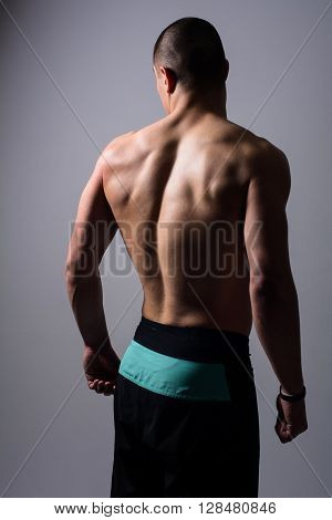 Portrait of muscular handsome young man from behind. Sporty man in the studio