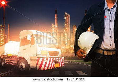 engineer holding hard hat standing against beautiful lighting of oil refinery in heavy petrochemical industry and big oil container truck use for petroleum industrial and land transport business