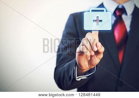Businessman touching and pressing first aid icon in the air with finger.
