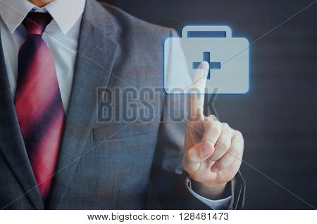 Businessman Touching And Pressing First Aid Icon In The Air With Finger