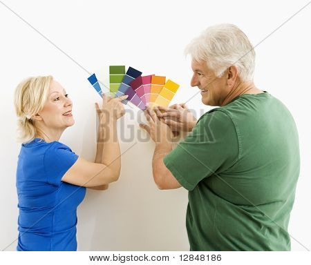 Middle-aged couple comparing and discussing paint swatches.
