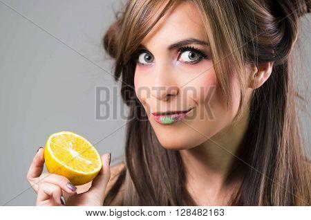 Headshot brunette with dark mystique look and green lipstick holding up an orange, grey background.