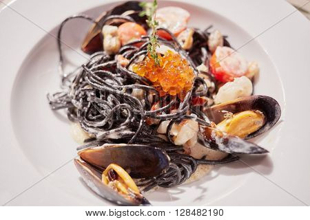 Mussels, red caviar and vegetables mix on white plate.