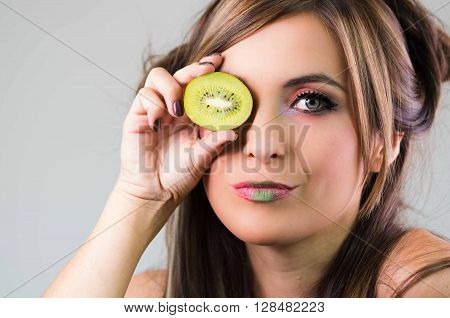 Headshot brunette, dark mystique look and green lipstick, covering one eye with open kiwi, looking into camera,