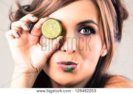 Headshot brunette, dark mystique look and green lipstick, covering one eye with open lime, looking into camera.